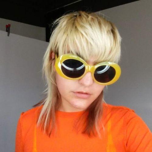 Joven con gafas grandes de sol amarillas y pelo capeado