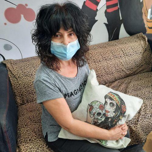Mujer con cojin de calaveras y mascarilla con pelo con mucho volumen