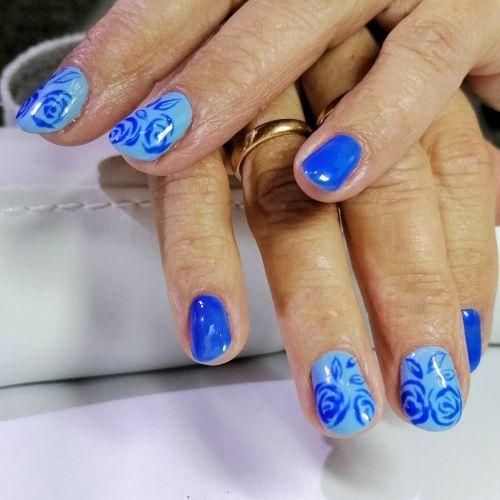 Uñas cortas en azules con garabatos de rosas