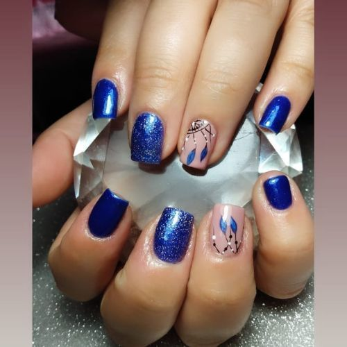Uñas azules con brillo y atrapasueño de plumas