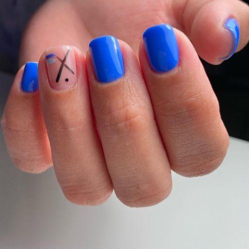 Uñas cortas azules con una uña sin pintar y detalles