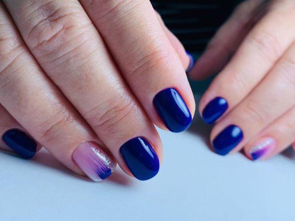 Uñas en azul intenso con uña clara decorada