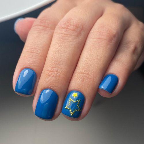 Uñas cortas en azul con estrella de piedrecitas doradas