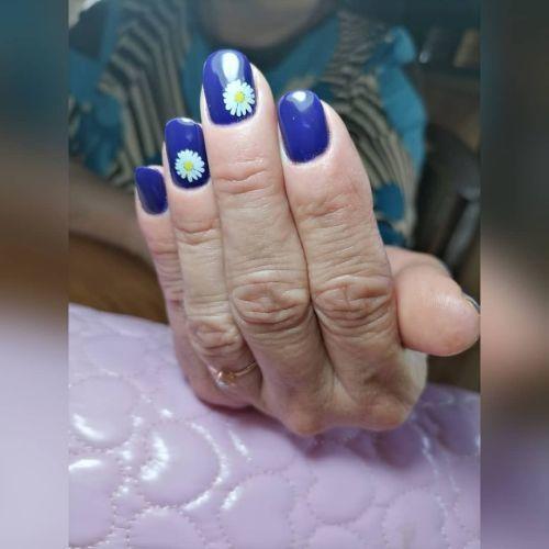 Uñas cortas en azul oscuro con margaritas