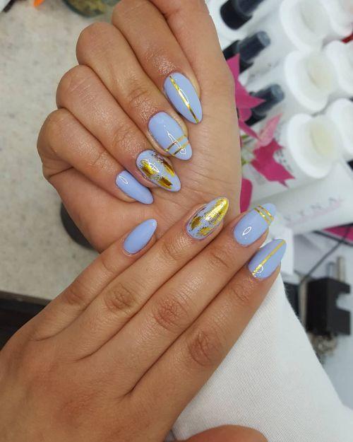 Uñas de gel en azul decoradas con dorado