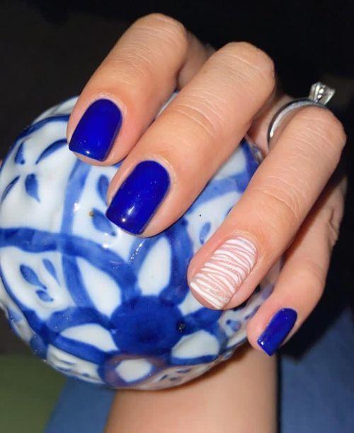 Uñas cortas de gel en azul con una uña en diseño de blancos