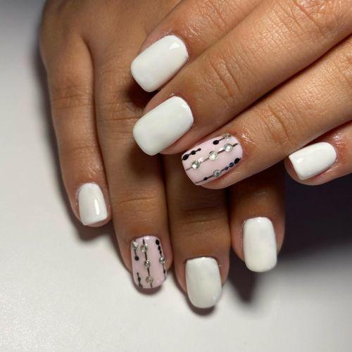 Uñas cortas blancas y rosadas con diamantes y líneas negras
