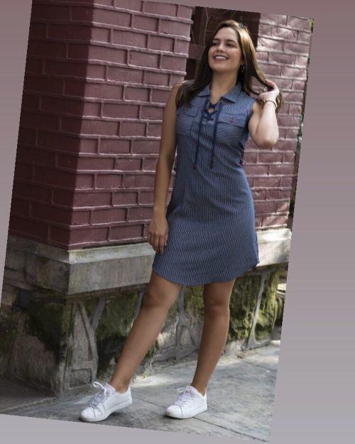 Mujer con vestido azul y zapatillas blancas