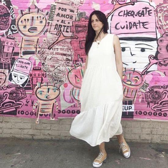 Mujer con vestido largo blanco y zapatillas color crema
