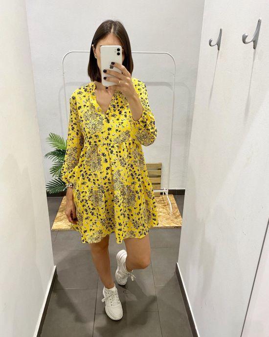 Vestido corto amarillo de flores y zapatillas blancas