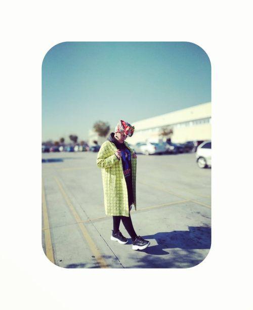 Mujer con abrigo largo y zapatillas y pañuelo en la cabeza