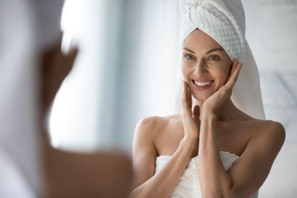 Mujer con toalla en la cabeza, admira su rostro