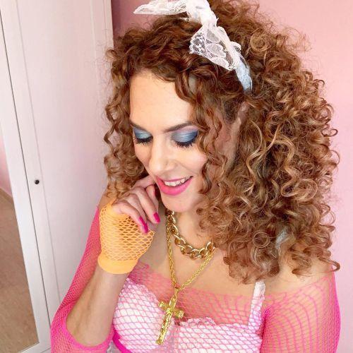 Mujer con diadema y rizos vestida de rosa