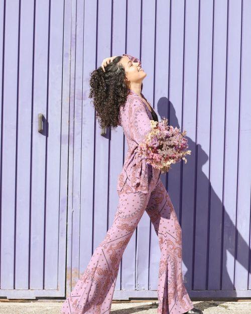 Mujer con mono lila y rizos