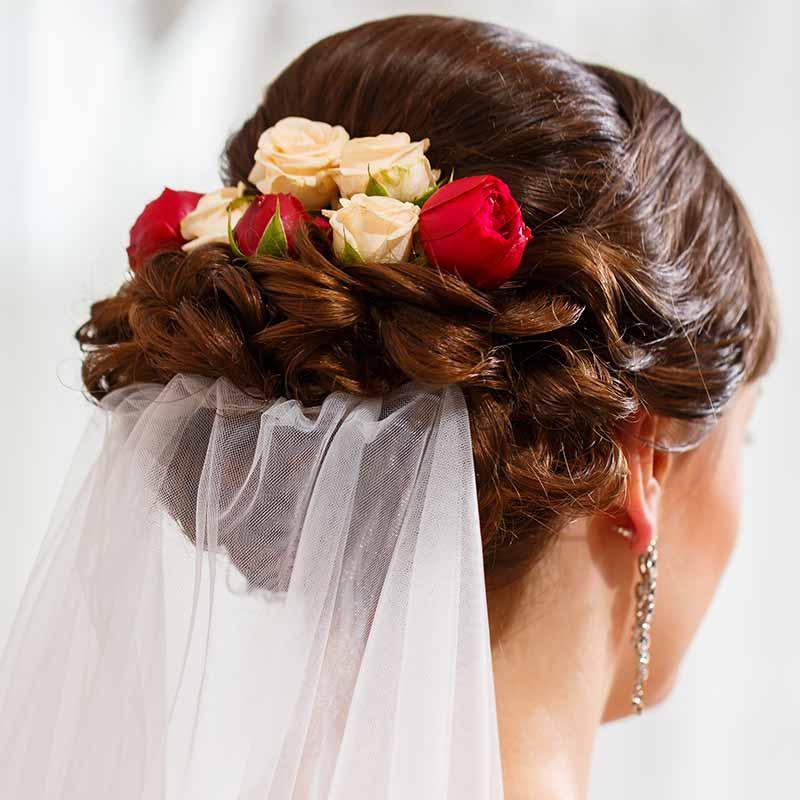 Recién casados con velo de flores capelli raccolti