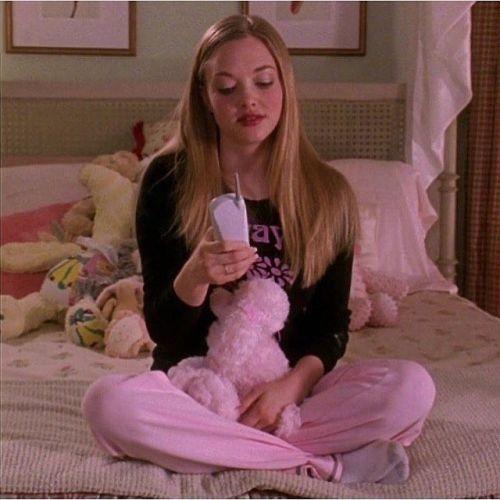 Joven sentada en la cama con pantalones y osito rosa