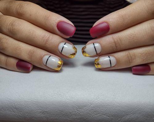 Uñas roja y blanca con adornos en dorado y plata