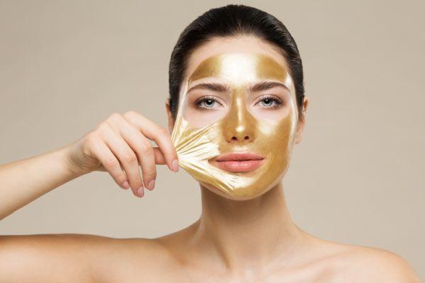 Mujer con mascarilla facial de oro